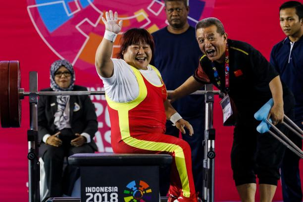 female powerlifter Xu Lili waves and smiles while sitting on the bench