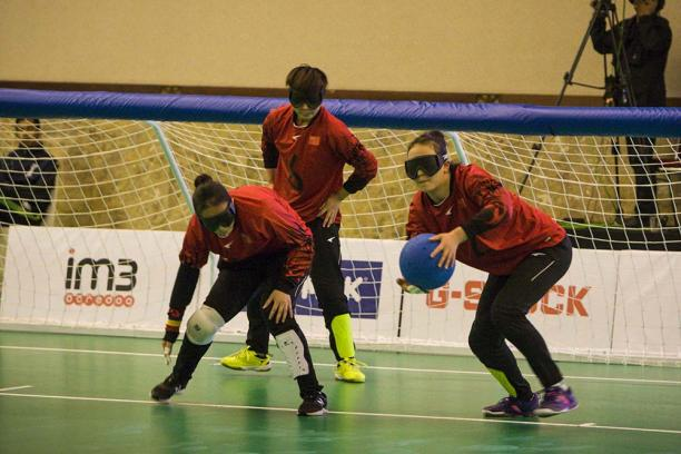 three female Chinese goalball players talking in front of the goal