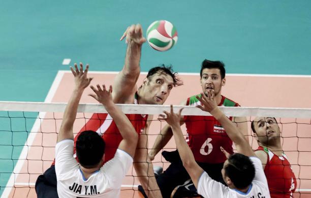 male sitting volleyball player Morteza Mehrzadselakjani blocks a ball over the net