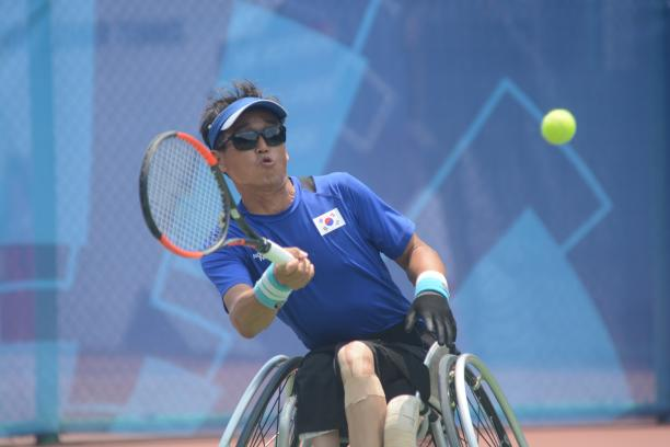 male wheelchair tennis player Kyu-Seung Kim plays a forehand