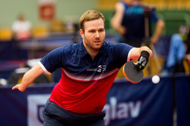 male Para table tennis player Peter Rosenmeier plays a forehand