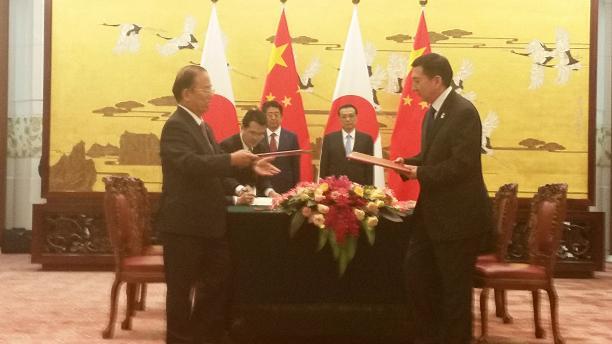 Beijing 2022 and Tokyo 2020 men in suits in a room exchanging documents