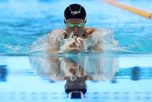 female Para swimmer Amilova Fatimakhon takes a breath during a breaststroke