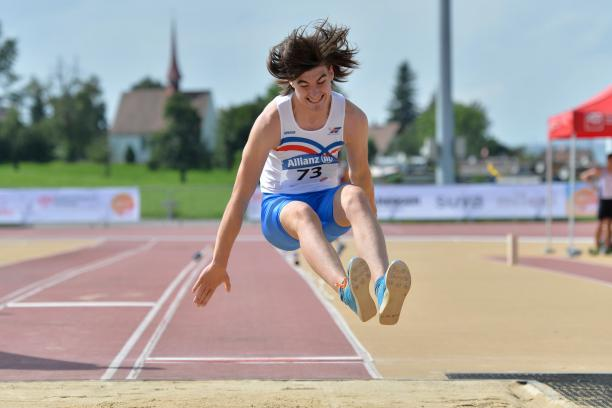 a male Para athlete jumps into a long jump sandpit