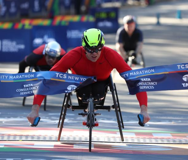 male wheelchair racer Daniel Romanchuk breaks the tape on the finish line ahead of two other wheelchair racers