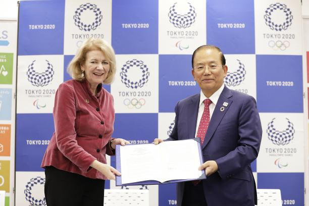 Tokyo 2020's Toshiro Muto and UN official holding a document together