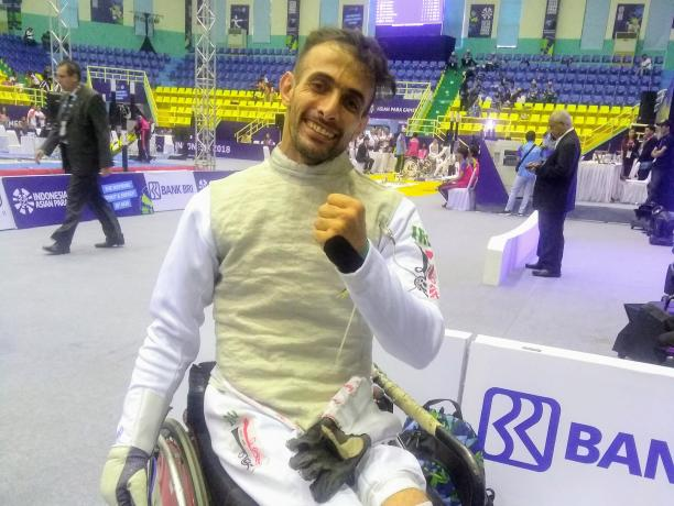 A man in a wheelchair wearing a fencing uniform