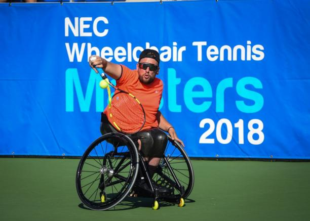 male wheelchair tennis player Dylan Alcott plays a backhand on a hard court