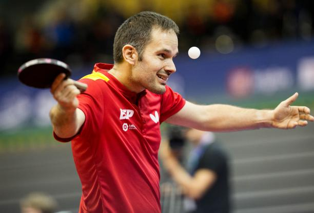 male Para table tennis player Jordi Morales raises his arms at the table