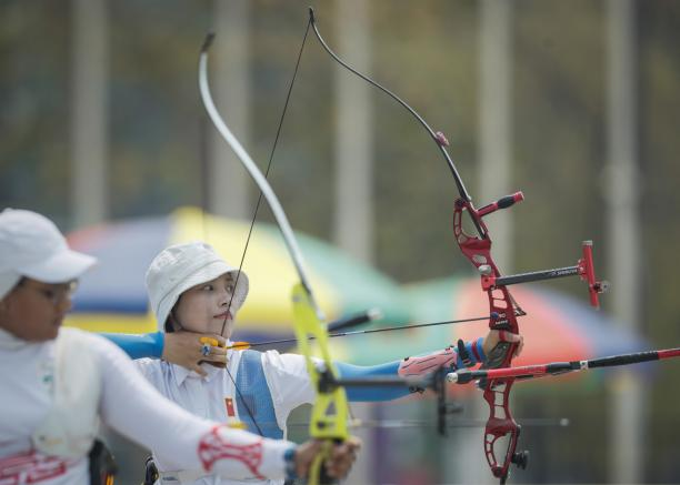 Chinese female archer pulls back her bow ready to shoot her arrow