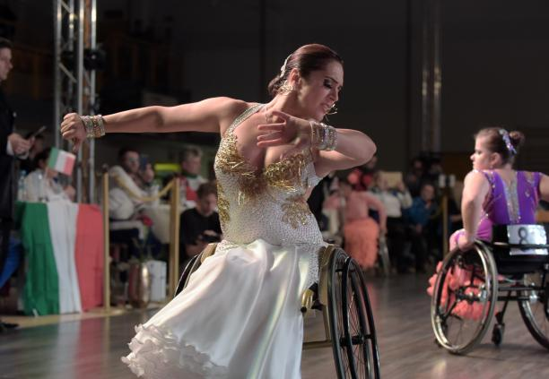 Ukrainian dancer in wheelchair wears glittering dress dances a conventional style