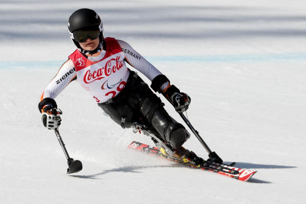 female Para alpine skier Anna-Lena Forster leans to the left as she skis down the slope