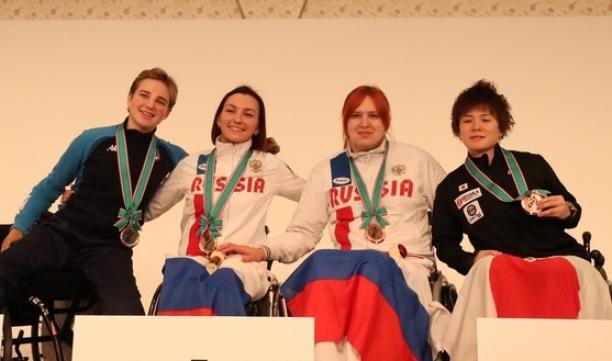 female wheelchair fencers Ludmila Vasileva and Beatrice Vio hugging on the podium