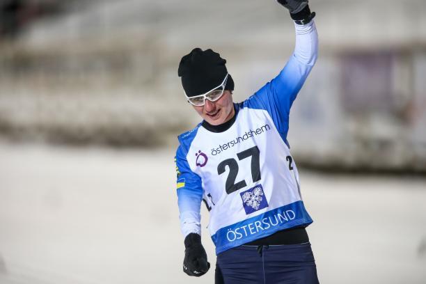 female Para biahthlete Oleksandra Kononova raises her fist in triumph as she crosses the finish line