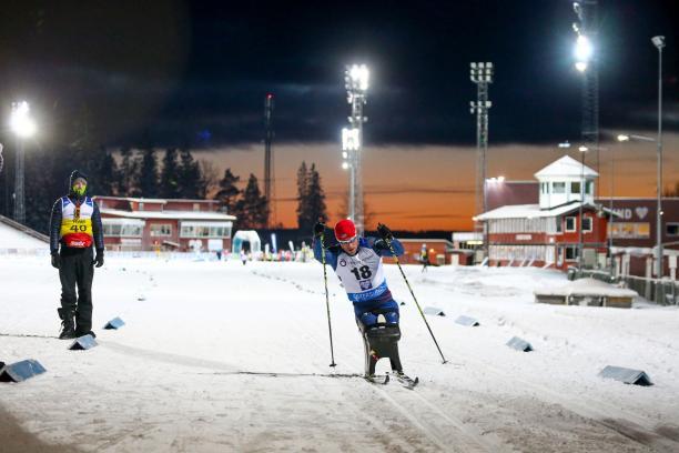 A man in a sitting ski competing in a biathlon race