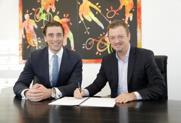 Two men smiling while one of the signs a contract