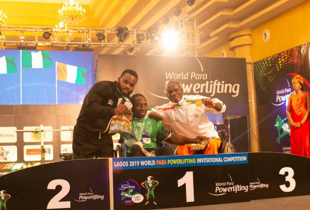 three male powerlifters, with Mufutau Rasaq in the middles, link arms on the podium