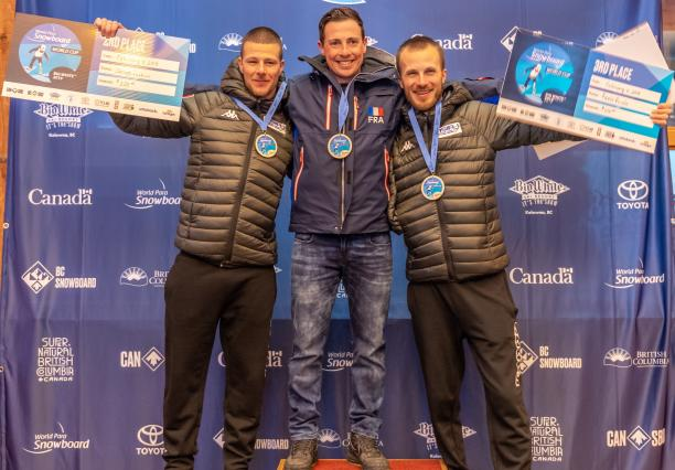 three male Para snowboarders with Maxime Montaggioni in the middle standing on the podium with their arms around eachother