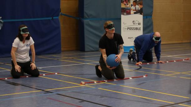 teachers with eyeshades play goalball in sport hall of the Bonn International School