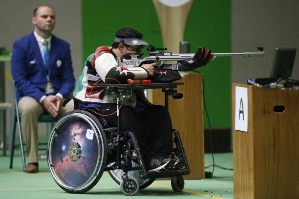 Man in wheelchair in a shooting range, targeting