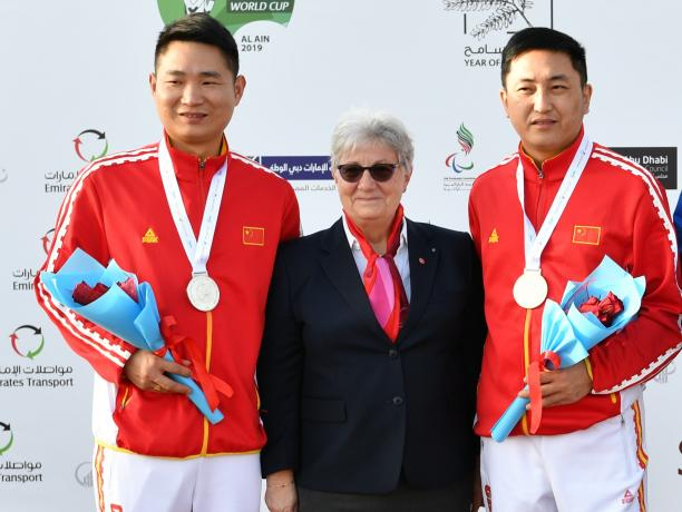 Chinese Para shooters Yang Chao and Huang Xing standing either side of a woman and smiling on the podium