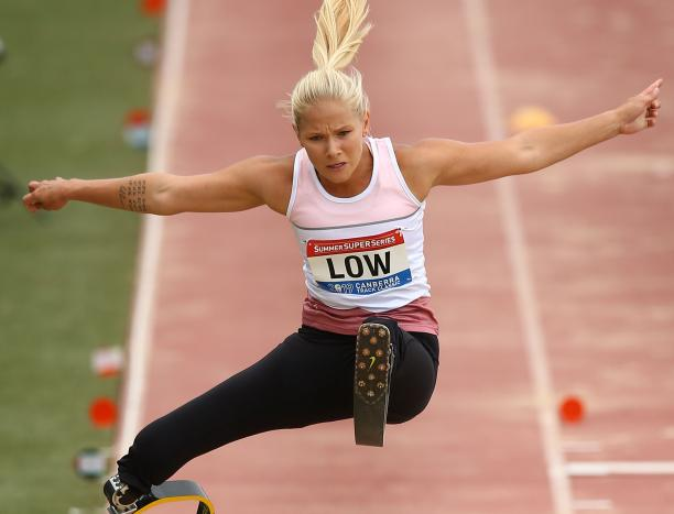 female Para athlete Vanessa Low jumps high above the long jump sandpit