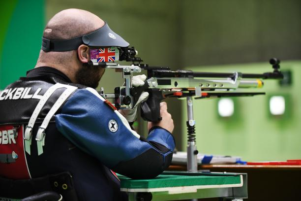 male Para shooter Ryan Cockbill prepares to shoot a rifle