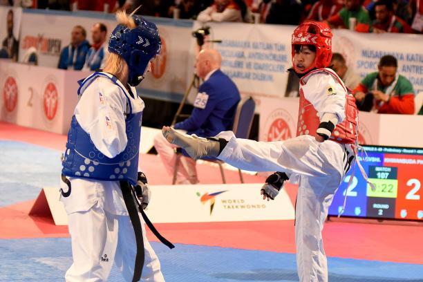 female Para taekwondo fighter Khwandusa Phuangkitcha kicks out towards another fighter