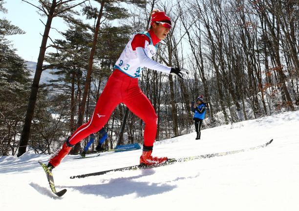 male Para Nordic skier Taiki Kawayoke skis through the forest