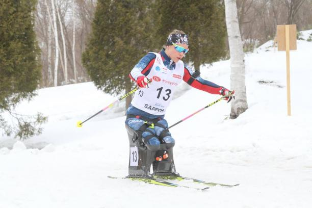 female Para Nordic sit skier Oksana Masters turns round a bend in the course