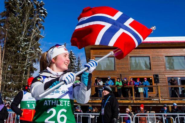 female Para Nordic skier Vilde Nilsen holds up a Norwegian flag