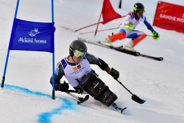 male sit skier Jesper Pedersen races head to head with a standing skier
