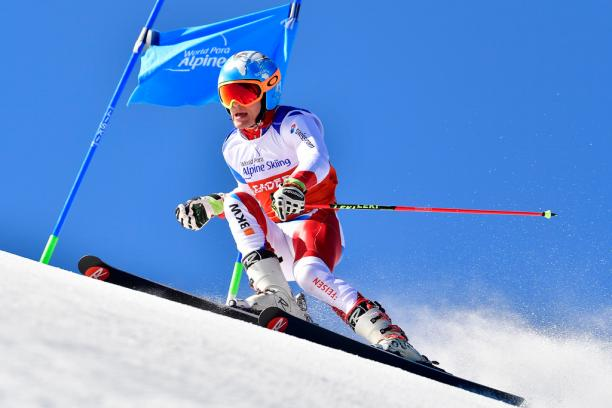 male Para alpine standing skier Theo Gmur skies through a gate