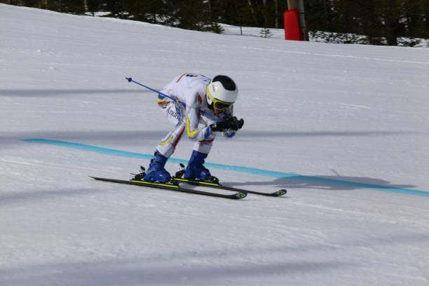 male Para alpine standing skier Roger Puig Davi crouches down as he crosses the finish line