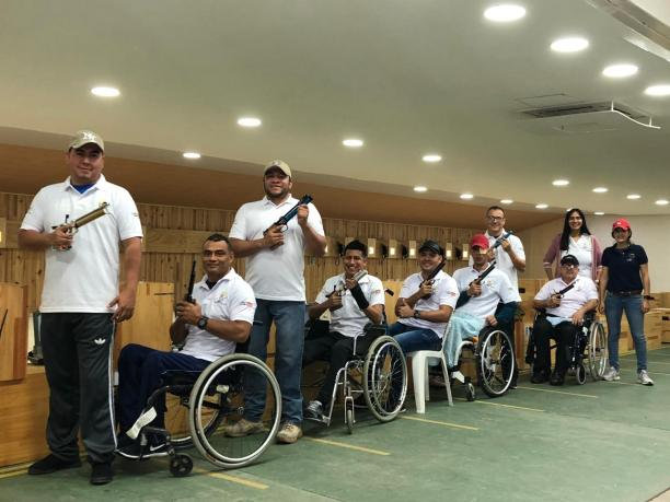 a group of male and female Para shooters from Colombia next to the target range
