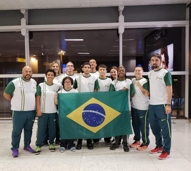 female Para taekwondo fighter Debora Menezes with other fighters holding a Brazilian flag