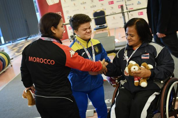 three female powerlifters shaking hands together on the podium
