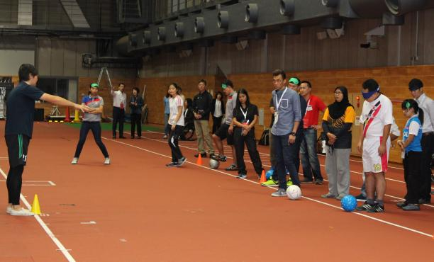 A group of people standing on a court blindfolded