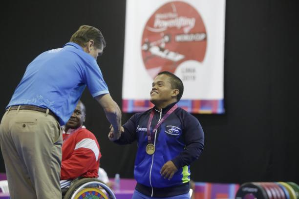 male Para powerlifter Herbert Aceituno shaking hands with an official