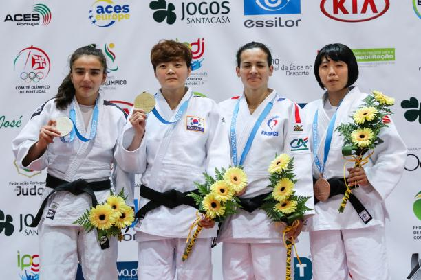 female judoka Sandrine Martinet on the podium holding her medal