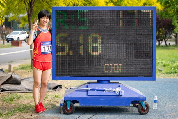 Chinese woman stands next to digital board displaying her world record