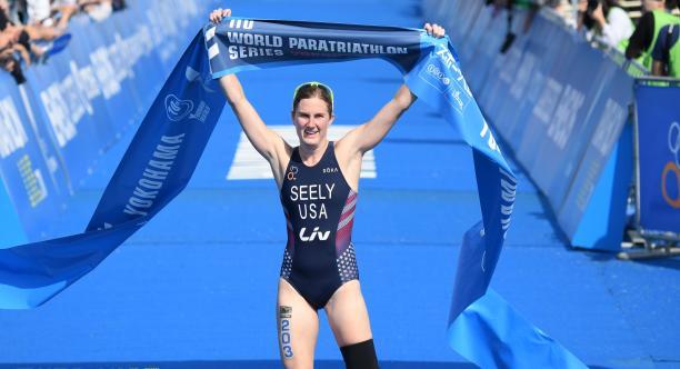 Female triathlete with left leg amputation celebrates as she crosses the finish line