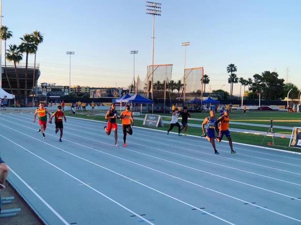 Four male vision impaired runners and thir guides racing on a track