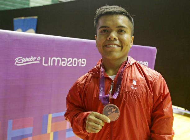 Diego Quispe smiles while he holds the bronze medal he won at the Lima World Cup