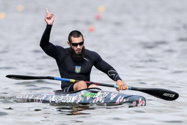 Serhii Yemelianov celebrates in the canoe with his hand in the air after winning gold