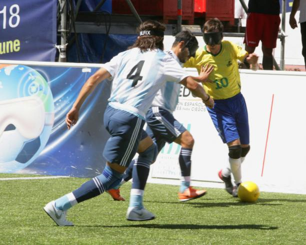 Ricardinho takes the ball while facing two Argentinian defenders