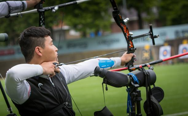 Korean male archer pulls back on his bow string aiming for a target