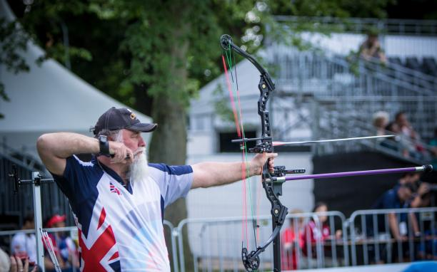 Man with long white beard shoots his bow and arrow