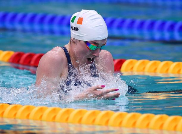 A female swimmer with a cap showing the flag of Ireland