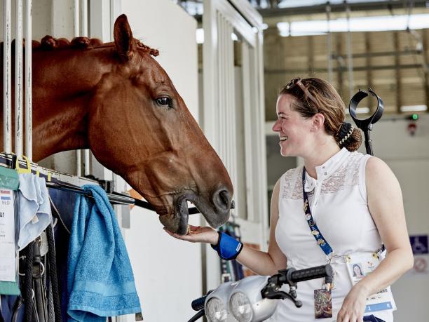female Para equestrian rider Sanne Voets feeding her horse
